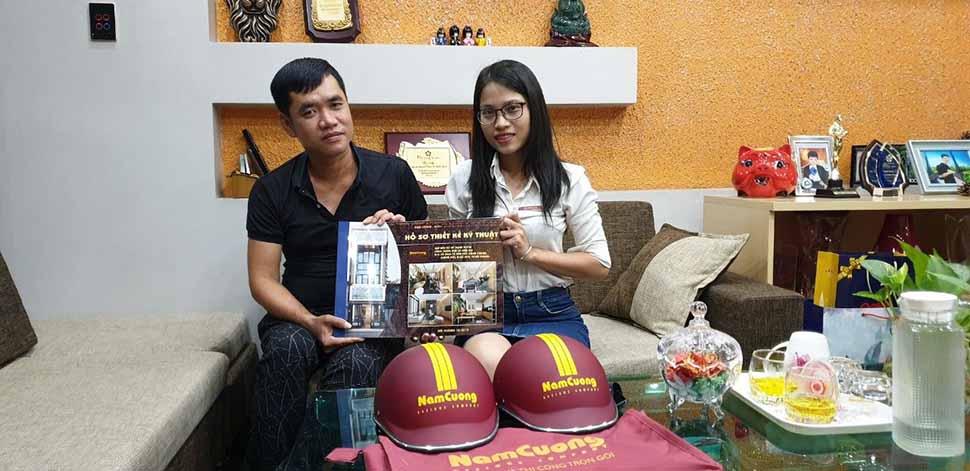 Nhân viên công ty Nam Cường bàn giao hồ sơ thiết kế kỹ thuật nhà ống hiện đại cho anh Tuyên