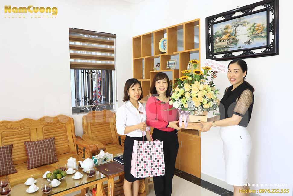 Chị Phạm Bích Ngọc -PGĐ công ty (ngoài cùng bên phải) tặng hoa chúc mừng tân gia chị Huệ (áo đỏ)
