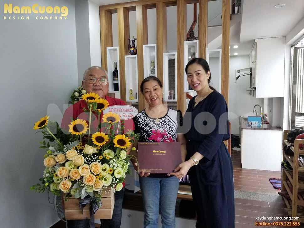 Chị Phạm Bích Ngọc-PGĐ công ty (ngoài cùng, bên phải) tặng hoa và quà chúc mừng tân gia cô Hiền (ở giữa)